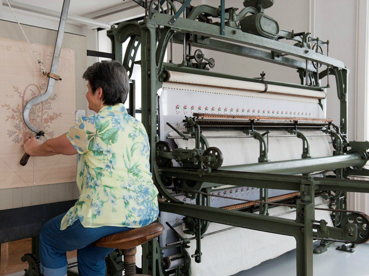 Woman operating the pentograph of a hand embroidery machine, Textielmuseum St Gallen.