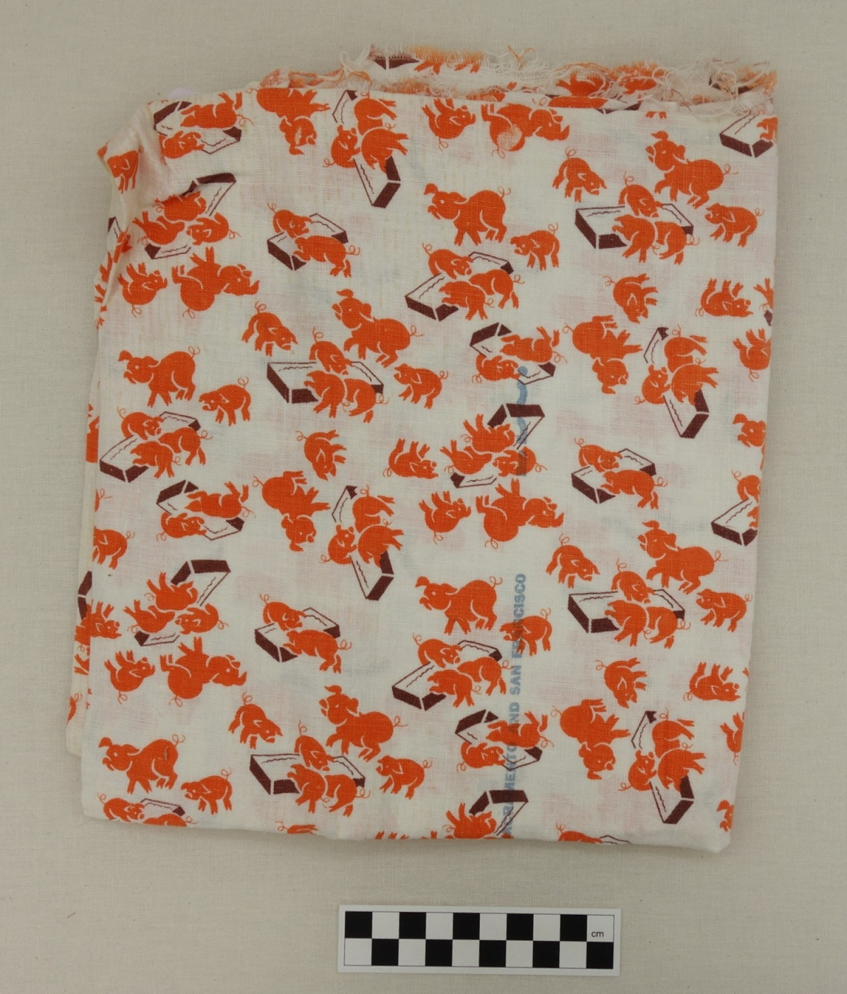 Length of cotton cloth with a design of orange pigs of various sizes eating at brown troughs. USA, mid-1950's (TRC 2017.1366).