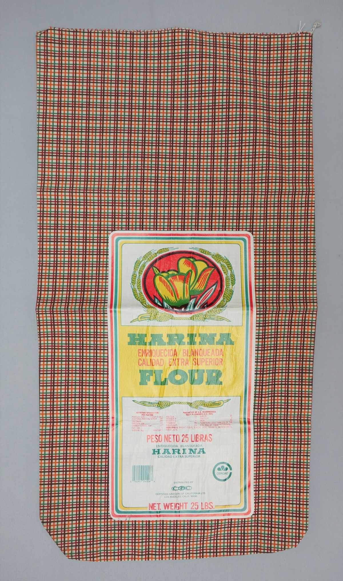 Large sack made from cotton with a printed checked design in brown, dark red, green and orange. With barcode. USA, 1960's (TRC 2017.3013).
