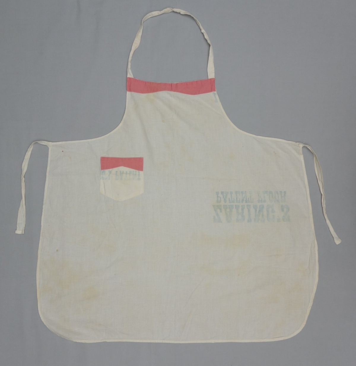 Bibbed apron with a small pocket made from bleached flour sacks. Parts of the bib and the pocket have been decorated with applied cotton cloth in pink (TRC 2017.3307).