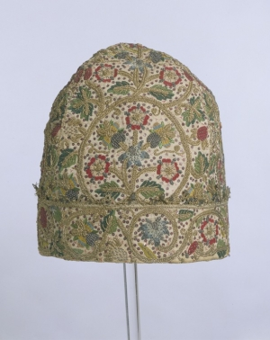 An early seventeenth century embroidered nightcap for a man. It is decorated with silk and metal thread embroidery and spangles.