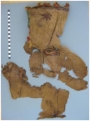 Remains from the site of Kellis, Egypt, of an embroidered tunic with hood placed on the body of a baby with a reconstruction, below, of how it would have been worn (object number 31/420-C5-2/272, 4th century.