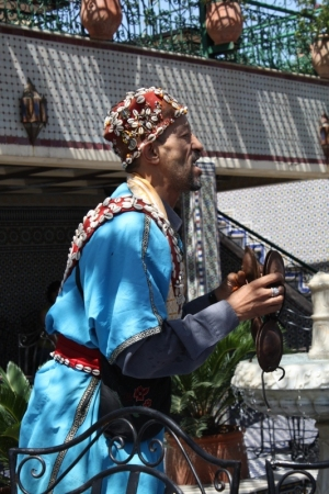 A Gnawa musician in a traditional outfit with beadwork, cowry shells, embroidery and tassels.