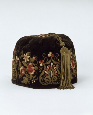 A smoking cap from the 1860's, made in South America for the Portuguese market. It is made from embroidered velvet and lined with silk, the long tassel is also of silk