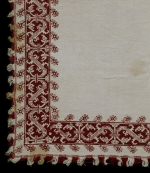 An example of 18th century Cyprian red work embroidery, possibly from Lefkara. The image shows the corner of a bed cover. It is made from linen that is embroidered with dark red silk using long-armed cross stitch, italian cross stitch, double running stitch and satin stitch.
