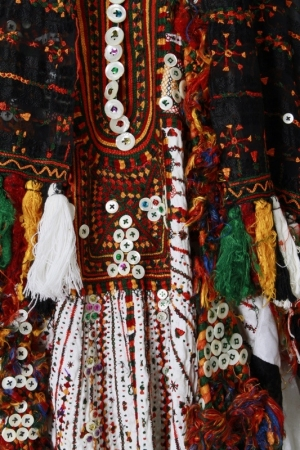 Detail of the embroidery on a black headdress and white wedding dress from the Siwa oasis, showing the traditional Siwa colours and the mother-of-pearl buttons, 1970's.