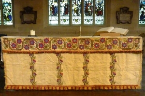 The Khaki altar cloth: An altar superfrontal worked in cross stitch on linen, made by the Khaki Club, now in Bradford Cathedral.