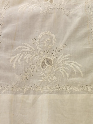 Detail of floral motif worked in Ayrshire whitewwork with central 'lace' insets surrounded by satin stitch flowers, stems, leaves, and small eyelets (c. 1825, Scotland)