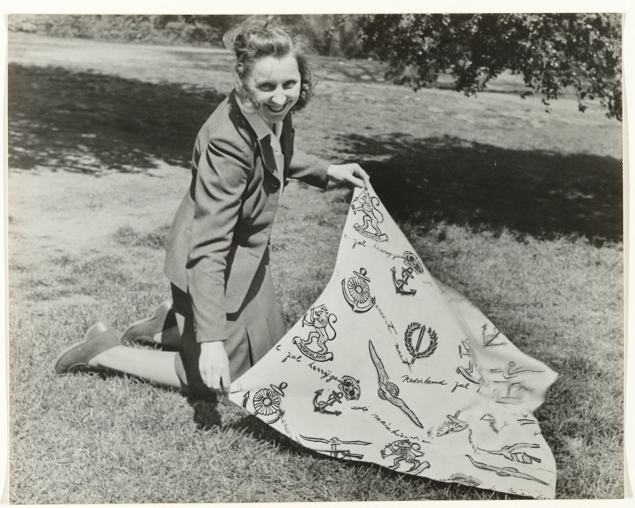 Photograph of a woman displaying the Red Cross scarf designed by Prince Bernhard  (Rijksmuseum, Amsterdam, NG-1988-9-20).