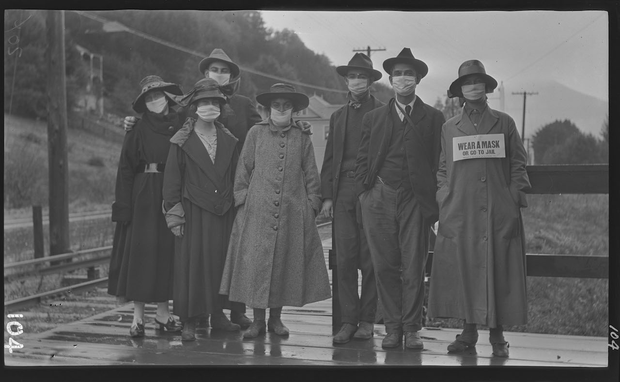"A group of people standing outdoors wearing masks over their mouths. This was probably during the Spanish Flu epidemic of 1918. One of the women has a sign in front of her reading 'Wear a mask or go to jail."" Courtesy Digital Public Library America."
