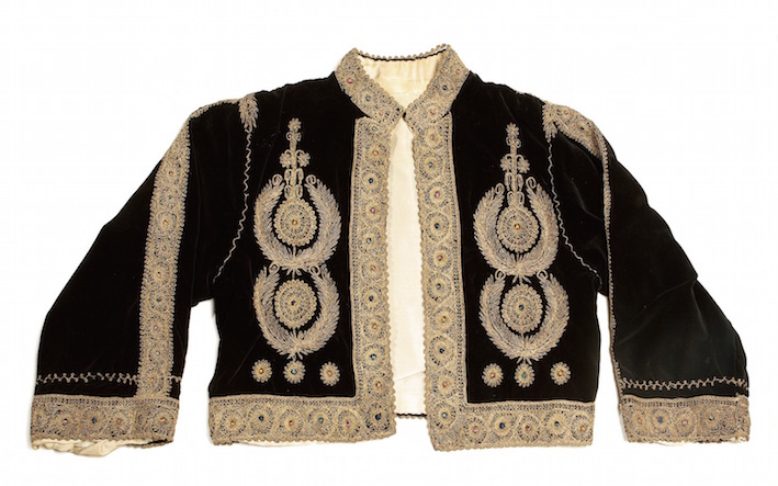 A Bethlehem jacket for a woman, based on a British military uniform jacket, complete with epaulettes and medals, worked in couching using gold thread with details in coloured silks (1920's, TRC 2004.0120).