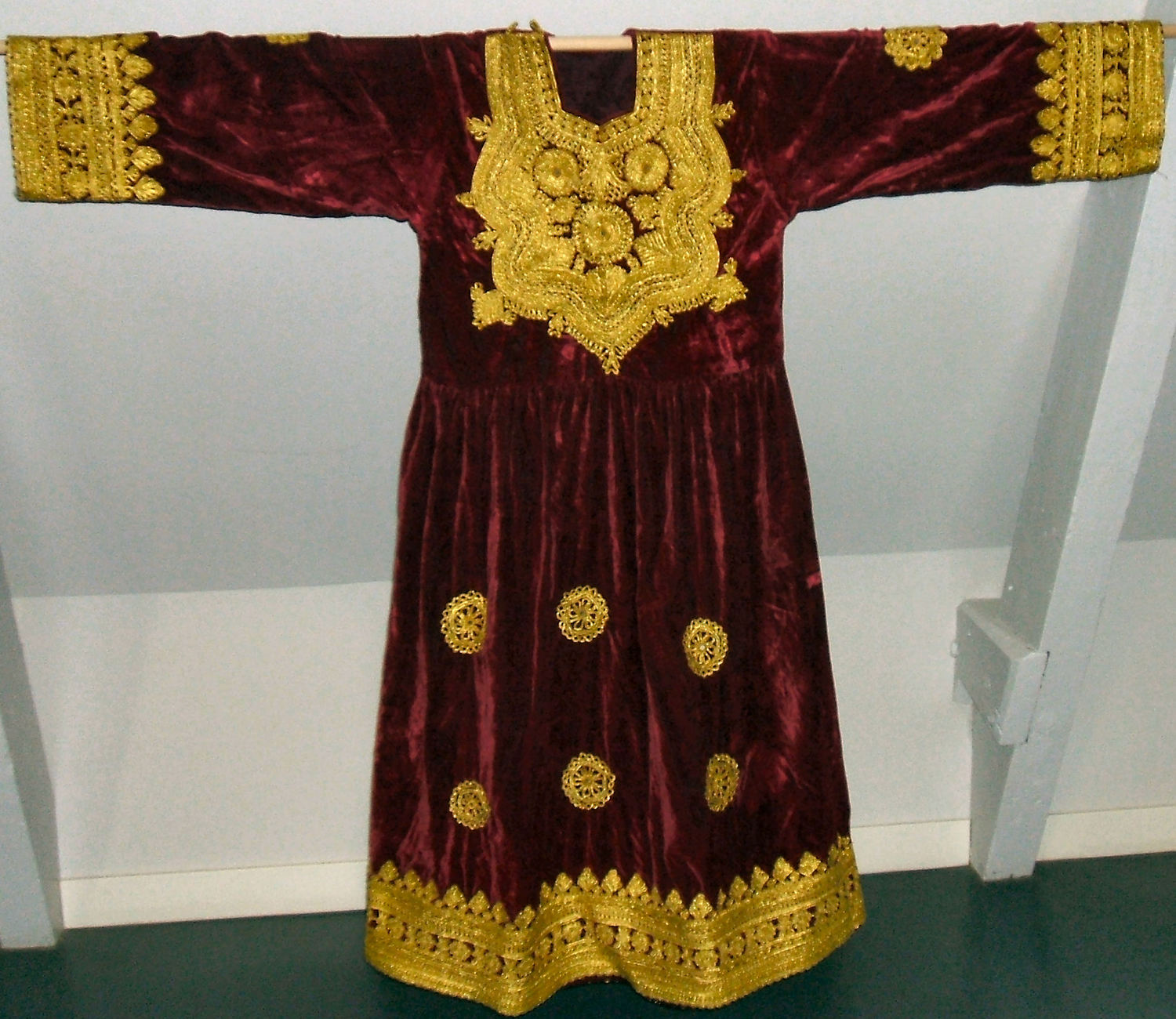 Pashtun dress. TRC 2007.0273b. Factory woven ground cloth with applied metal thread braid (passementerie).