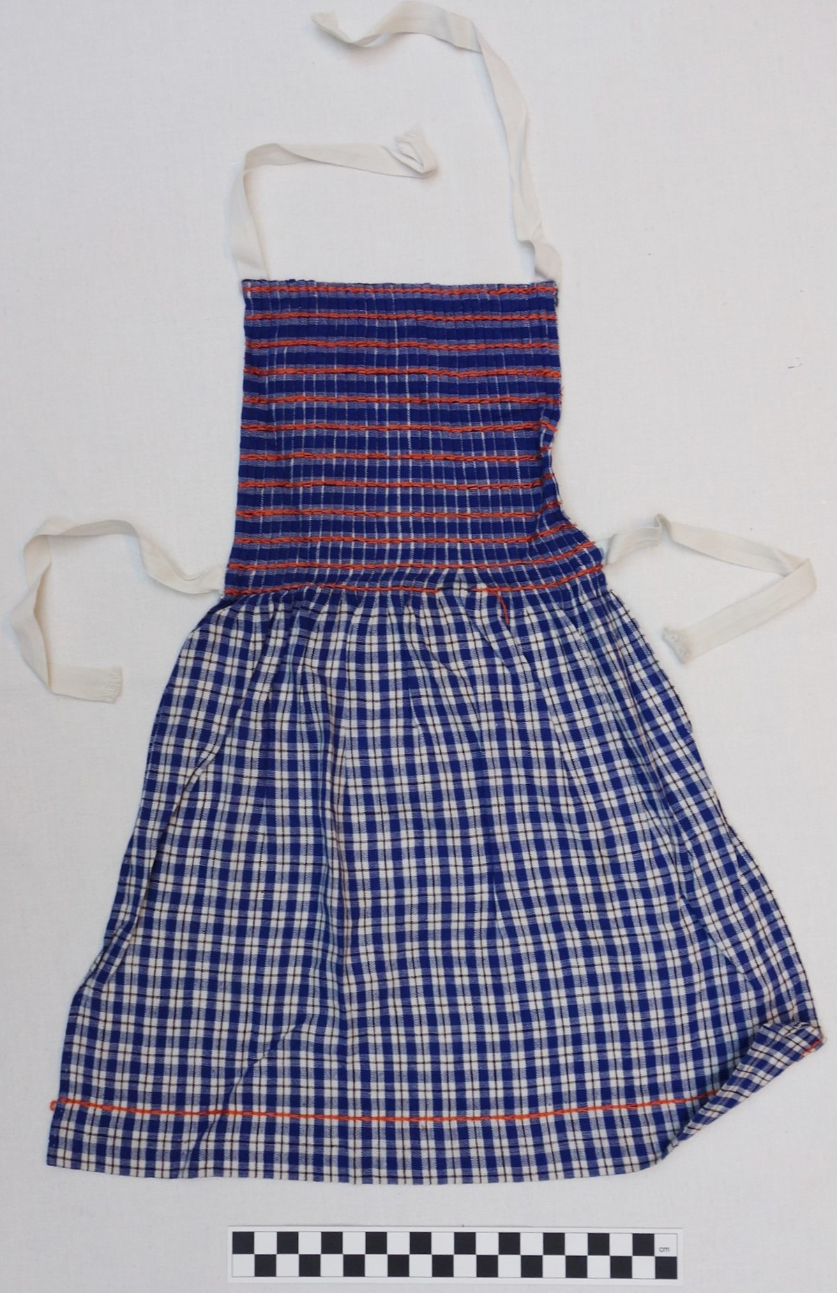 Girl's apron in orange, white and blue, early 1940s (TRC 2010.0569).