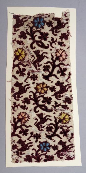 Sample of mid-17th century voided and ciselé velvet  with a design of dogs in a colourful forest (TRC 2011.0385).