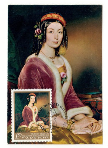 Postcard of an Hungarian painting by Borsos Jóseph, showing a woman wearing a red velvet jacket  with the same image on an Hungarian postage stamp (TRC 2018.2544).