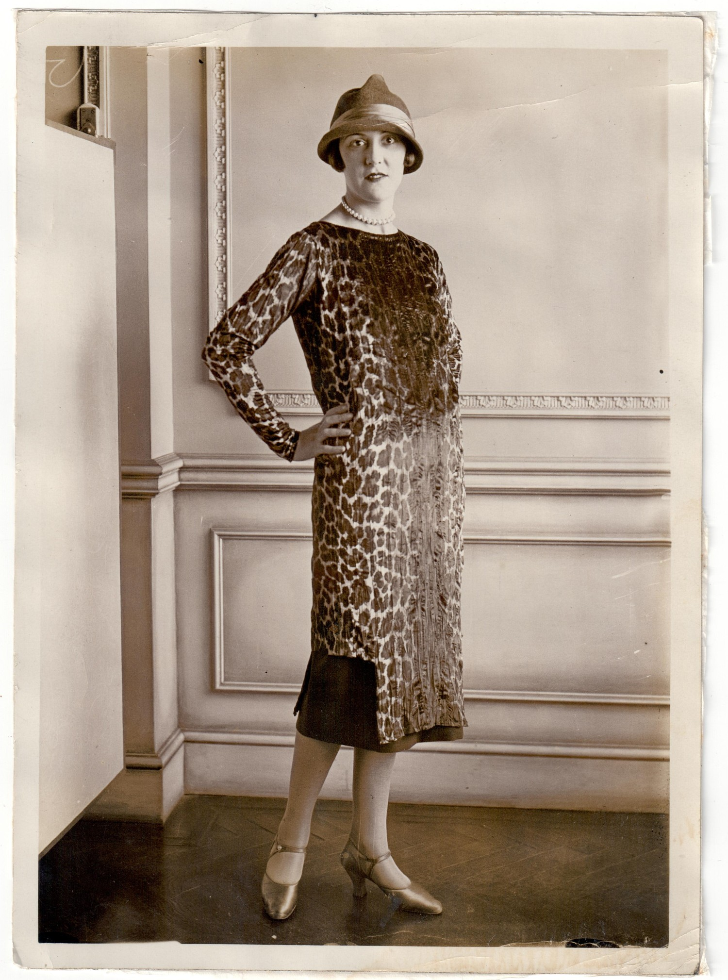 Photograph from the 1920s showing a professional model wearing a velvet dress with a design of leopard skin spots (TRC 2018.3137).