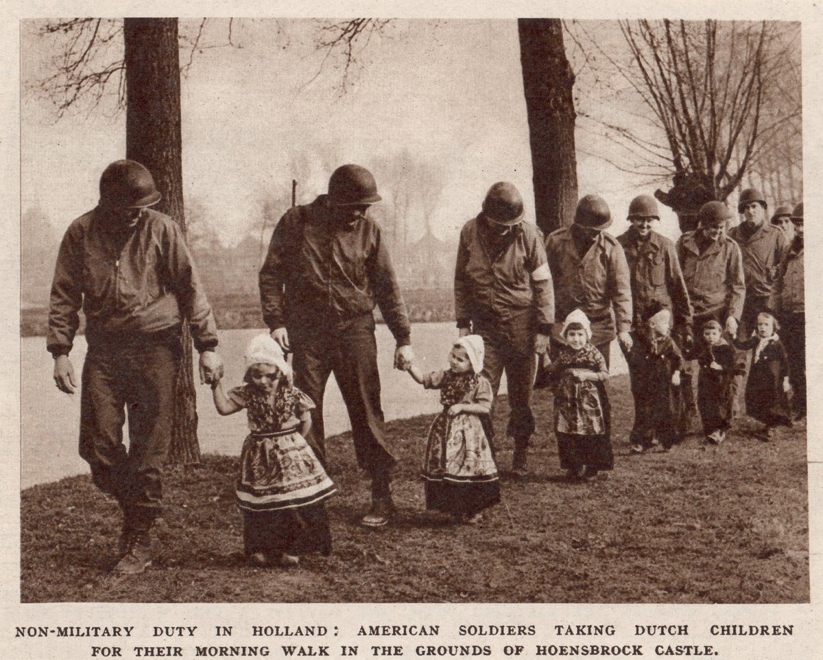 Photograph of a group of American soldiers and local children in Volendam-style costume. The photograph was taken in Hoensbroek, Limburg, The Netherlands, in 1945 or 1946 (TRC 2019.1424).