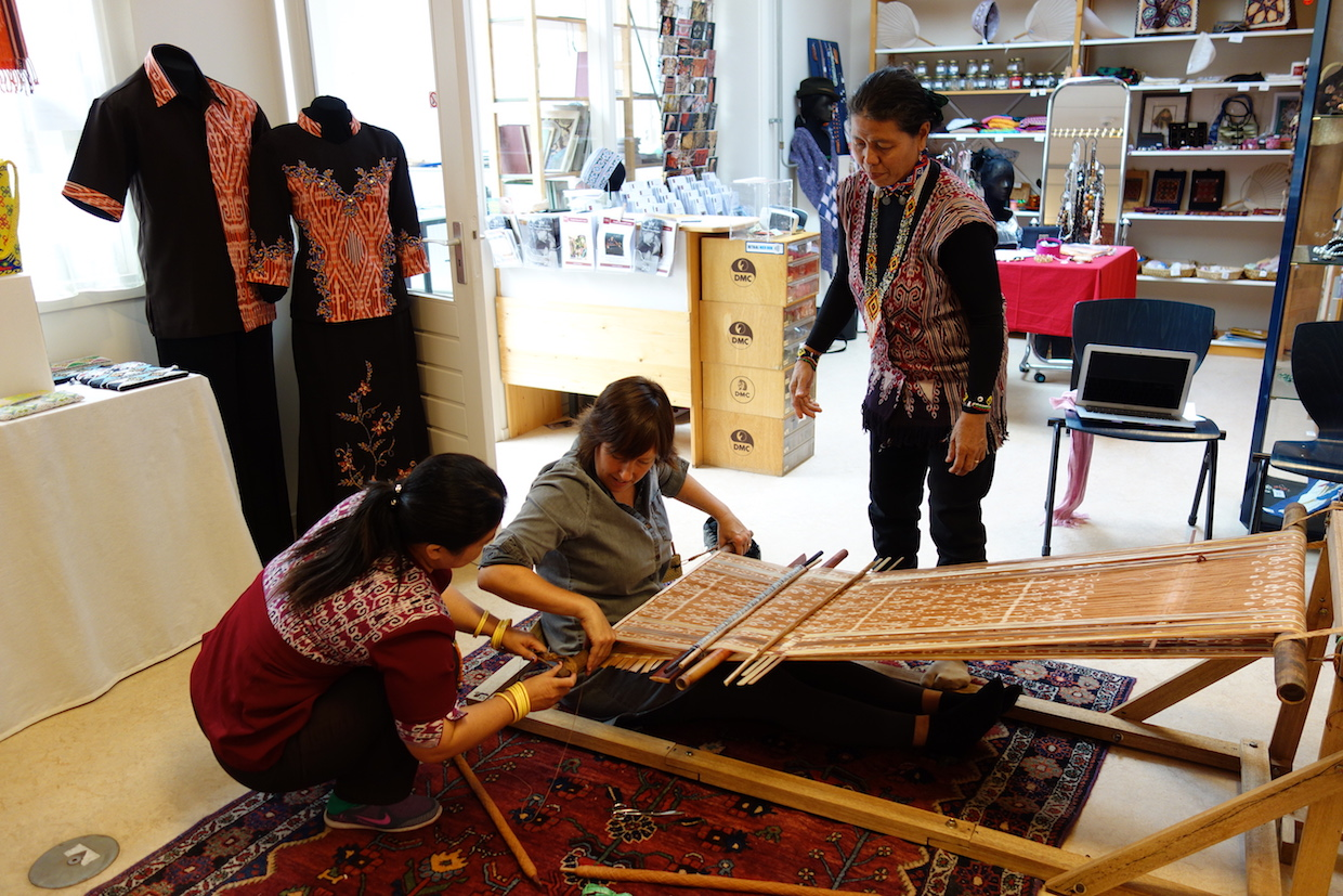 Participants to the ikat workshop having lessons on how to weave on a body-tension loom.