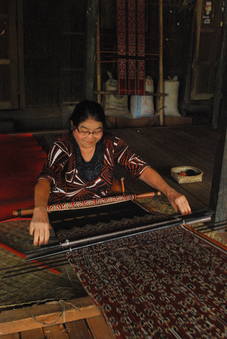 Craftswoman from Sintang Regency, Kalimantan, Indonesia, working on her loom making ikat cloth.