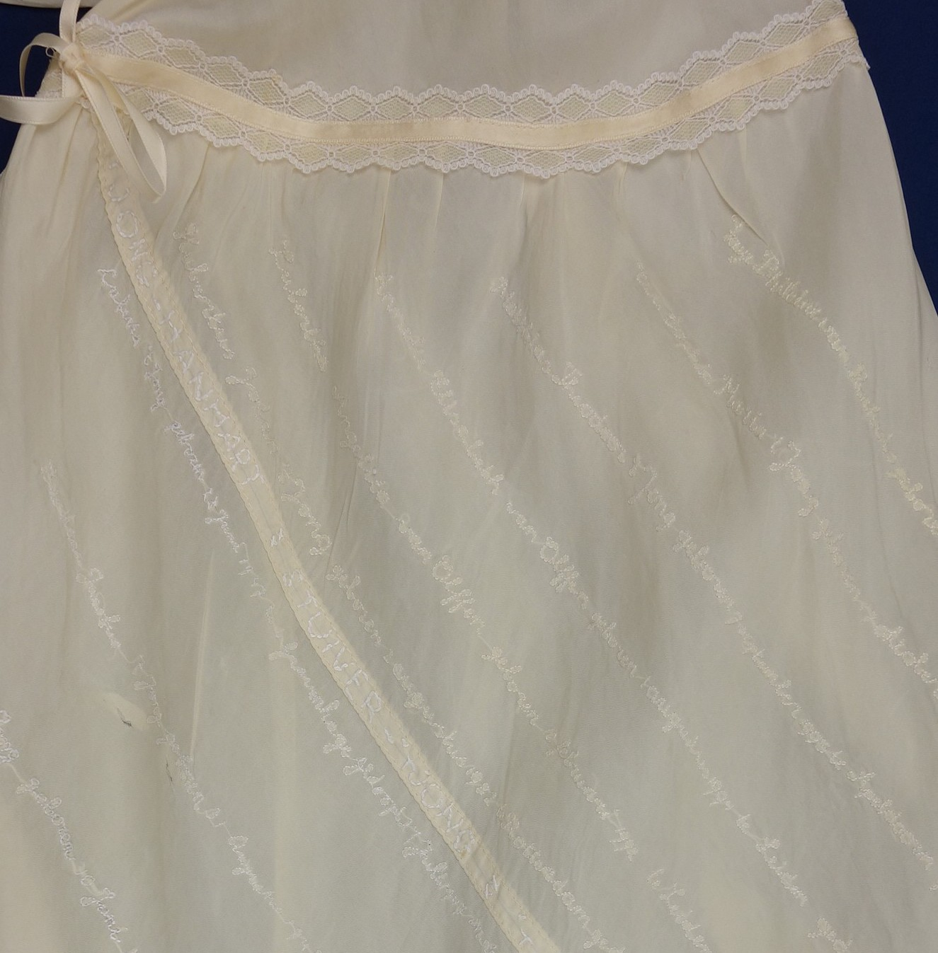 Detail of the christening gown, with the names of the baptised children embroidered in diagonal lines.