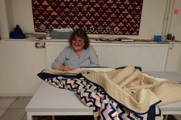 Beverley Bennett sewing on sleeves for the quilts (TRC October 2018).
